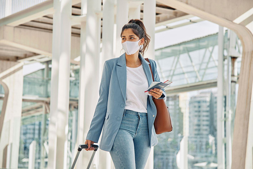 Mulher em aeroporto com máscara, bagagem e bilhetes de passagem.