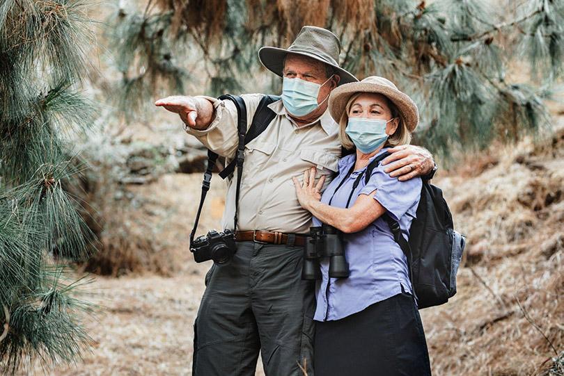 Casal viajando na natureza usando máscara.