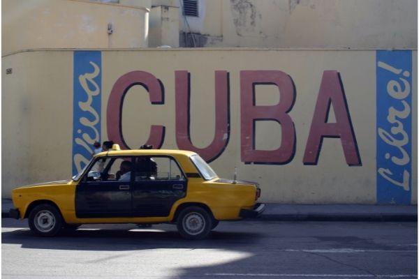 carro amarelo na frente de pintura em muro escrito cubra libre